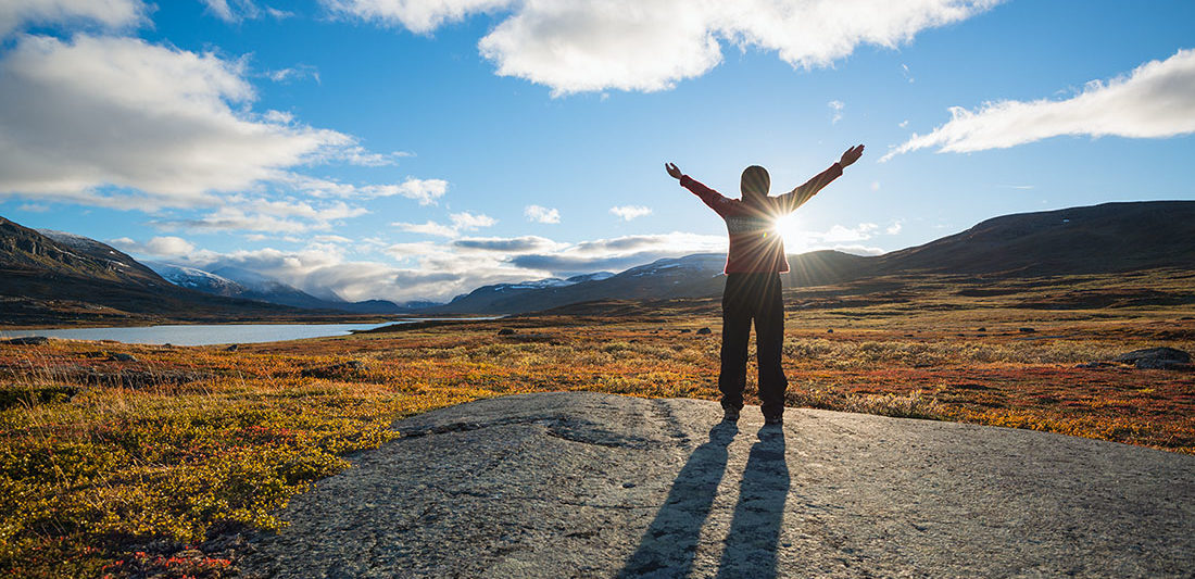 Female raises hands towards sun in Autumn mountain landscape along Kungsleden trail, Lappland, Sweden